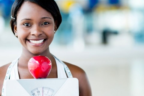 20617913 - healthy eating woman holding scale and an apple